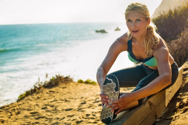 Woman Runner Stretching in Lifestyle Headshot